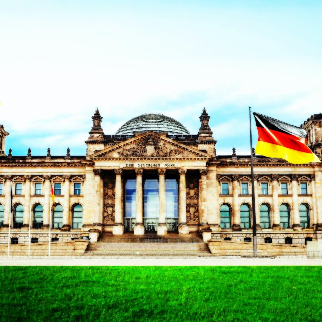 Bild des Bundestag-/Reichtagsgebäudes in Berlin mit Detuschlandfahne und Rasen davor.